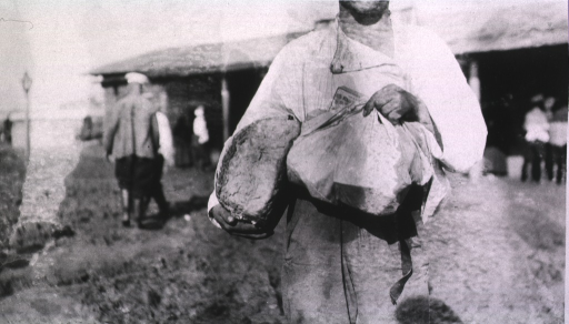 <p>A man holds a loaf of bread, a staple of life in Russia at the time.</p>