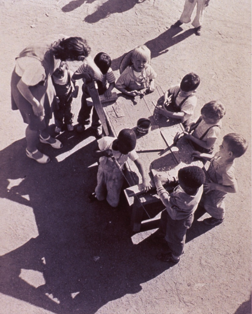 <p>Aerial view of several children working with saws and hammers at a table in an outdoor play area in Seattle.</p>
