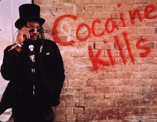 <p>Multicolor poster.  Visual image is a color photo reproduction featuring Michael E. Johnson standing in front of a brick wall; title text appears as graffiti on the wall.  Johnson was the co-founder of the Killer Bees, a reggae group.  Publisher information in lower right corner.</p>