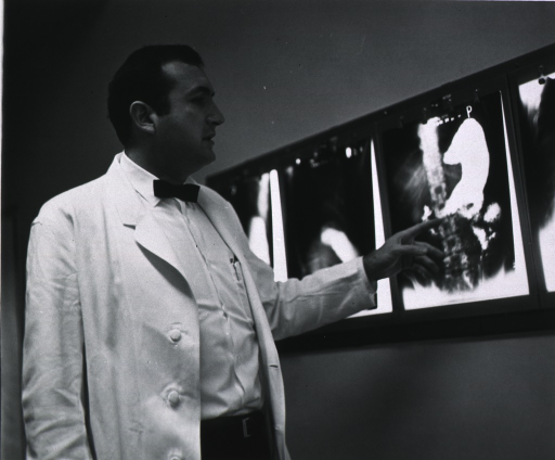 <p>Half-length, right profile, in lab coat, pointing to one of several x-rays illuminated beside him.</p>