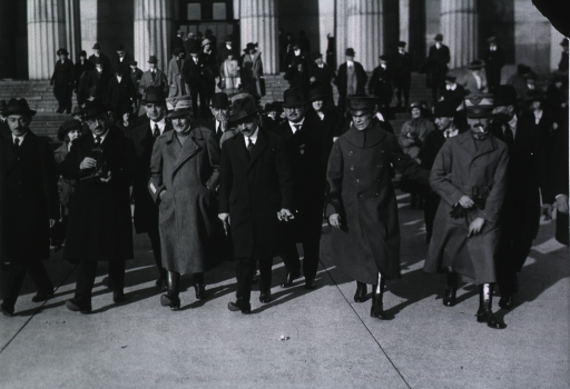 <p>Showing group of delegates leaving building, Diaz, 3rd from left in front row.</p>