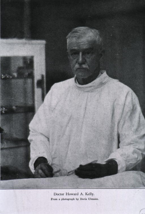 <p>Half-length, standing, left pose, full face; wearing operating gown and holding instruments.</p>