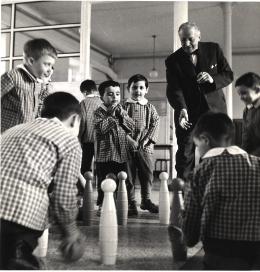 <p>Professor Parisot is playing a game with several children, who are all wearing uniforms, at the Child Rehabilitation Centre of Flavigny.</p>