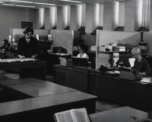<p>Interior view: Two women are typing at their desks, a third woman is looking through a card file, and Henry W. Brown is sitting at a desk in the background.  An open dictionary is in the foreground.  Partitions divide the work area.</p>