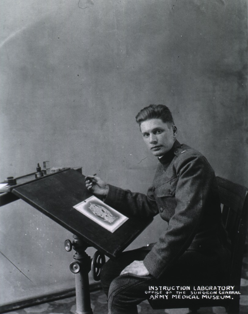 <p>Seated at drawing board, wearing uniform.</p>