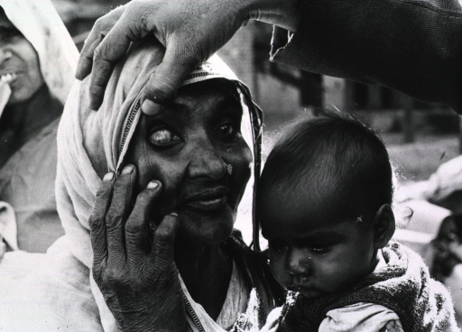 <p>An Indian woman, holding a small child, is having her eyes examined.</p>