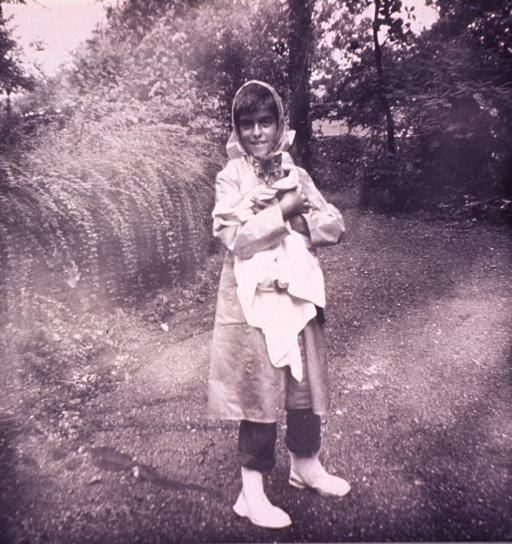 <p>Girl (full-length portrait, facing front) in kerchief, raincoat, and boots standing outdoors holding a cat wrapped in a towel.</p>