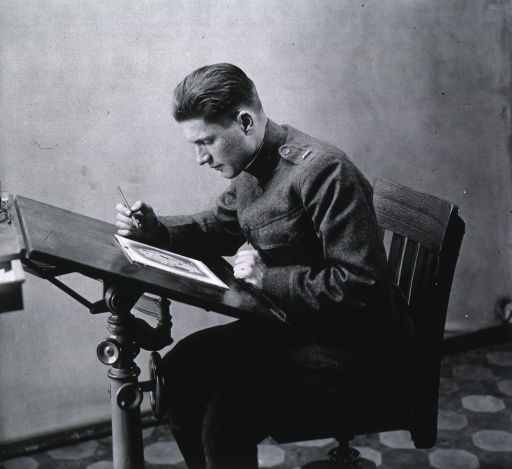 <p>Seated, leaning over drawing board, wearing uniform.</p>