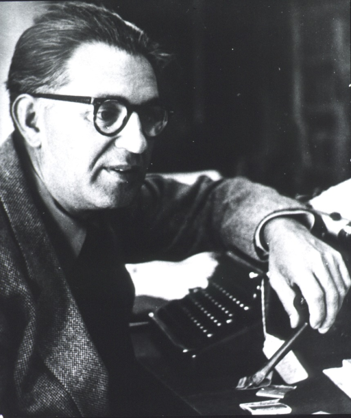 <p>Head and shoulders, right pose, wearing glasses, seated at typewriter, and holding pipe in left hand.</p>