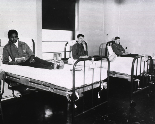 <p>The three men recline on their hospital beds.  One reads a comic book, another talks on the phone, and the third stares forward.  Two of the men hold cigarettes.  Each of the men is in his bare feet.</p>
