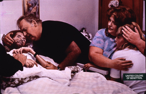<p>Multicolor poster with white and black lettering.  Visual image is a color photo reproduction depicting a bedside scene.  An emaciated man lies in a hospital bed.  An older, robust man leans over the bed and cradles the patient's head.  A woman and girl are nearby; the woman has the girl in a protective embrace.  Title near lower right corner.  Poster was part of an ad campaign for Benetton and is entitled &quot;AIDS&quot; according to Benetton press materials.</p>
