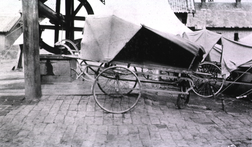 <p>A view of a covered wheeled litter.</p>