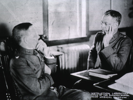 <p>Half-length, seated at desk, left profile; hand to face; elbow resting on desk; talking to unidentified person.  Both wearing uniforms.</p>