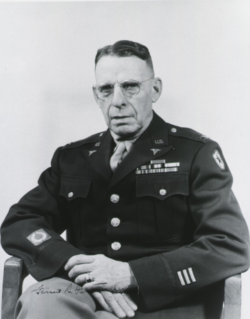 <p>Seated, full face, uniform, colonel, hands clasped in lap.</p>