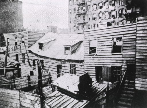 <p>Exterior view: rear of buildings that face Baxter Street; the buildings are in disrepair, and in general, unsanitary conditions prevail.</p>