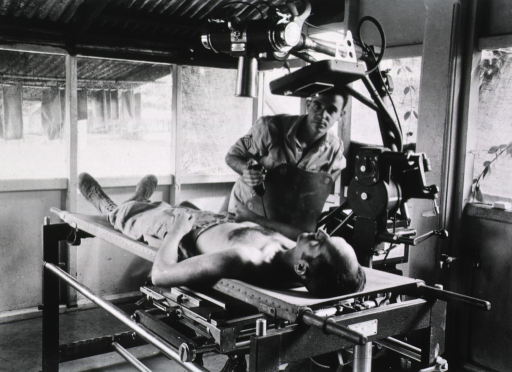<p>A male technician prepares a shirtless man lying on a table for an X-ray.</p>