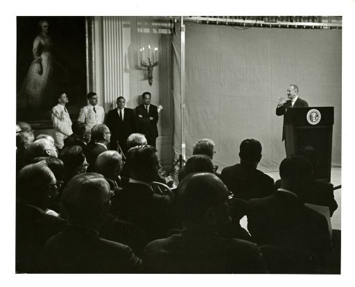<p>President Lyndon Johnson speaks at a White House gathering from the podium to discuss the 1965 Medicare Bill.</p>