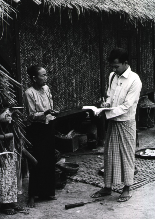 <p>A man and a woman are standing outside a hut; the man is checking off the names of villagers requiring treatment for trachoma.</p>