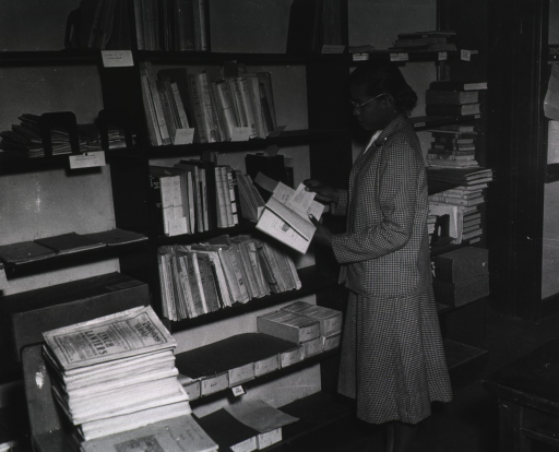<p>Interior view: In the processing section Miss Meeds is standing in front of bookshelves comparing a catalog card to the title page of a book.</p>