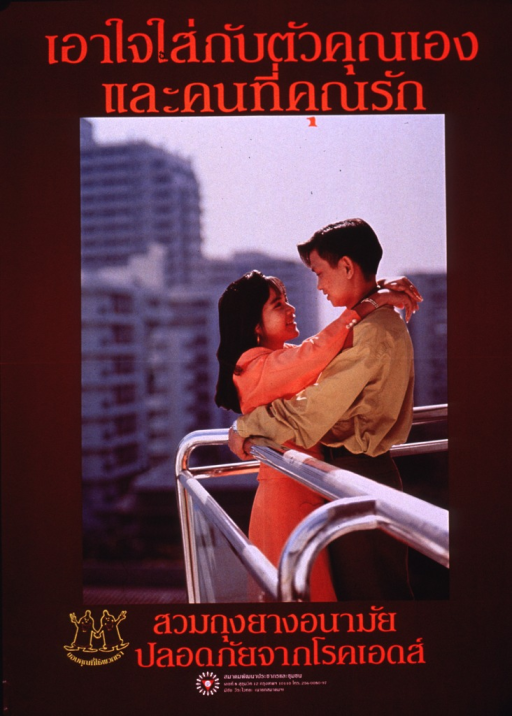 <p>Predominantly maroon poster with multicolor lettering.  Lettering appears to be in Thai script.  Some text at top of poster.  Visual image is a color photo reproduction featuring a young, male-female couple standing on a balcony and embracing.  Additional text, logo of two smiling condoms, and publisher logo at bottom of poster.</p>
