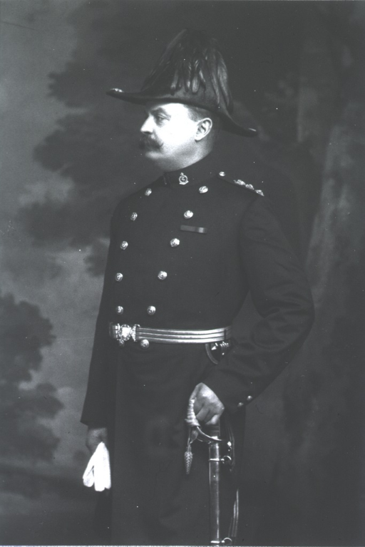 <p>Standing, wearing full officers dress uniform, gloves in right hand.</p>