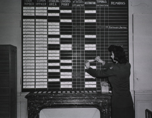 <p>A U.S. servicewoman places tags on the board indicating the starting points and destinations of hospital trains in cities throughout France.  The board is in English.</p>