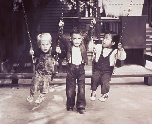 <p>Three children in a playground; two of the children are on swings, the third child is between the other two.</p>