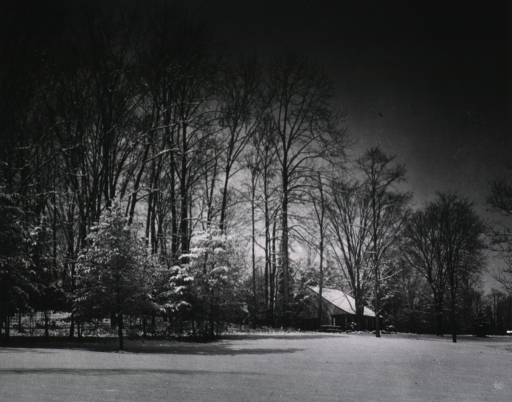 <p>Wintertime photo of Top Cottage in its original location atop the wooded hill on which the Clinical Center now stands.</p>
