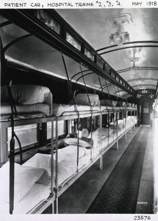 <p>Two tiers of beds are positioned against one side of the train car.  Only one of the beds is occupied:  a serviceman lies under the sheets and reads a book.</p>