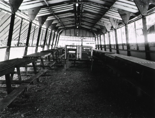 <p>Picnic tables line either side of the open-air hall.  There is a dirt floor.</p>