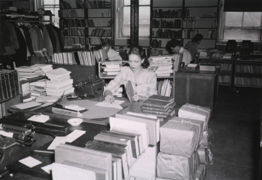 <p>Interior view:  Mrs. Greene is checking the spine title against a sheet on her desk.  Others are working at their desks.  Material is in wrapped bundles, on bookshelves, and on book trucks.</p>