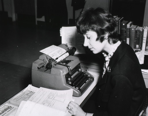 <p>Interior view: Woman sitting in front of a manual typewriter looking at a data sheet.  On her desk are language and medical dictionaries.</p>