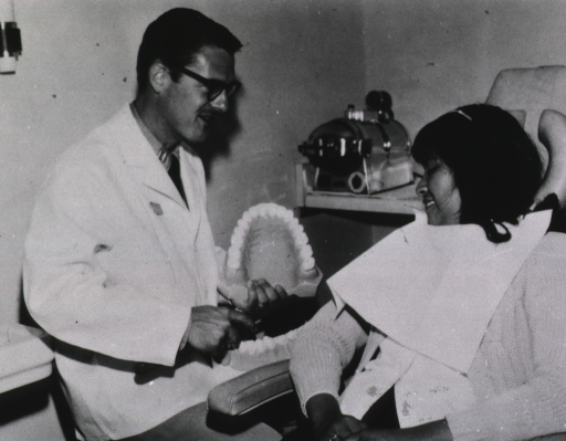 <p>Interior view of dental office: a dentist holding an oversized set of teeth discusses oral hygiene with a young girl sitting in a dental chair with a paper bib around her neck.</p>