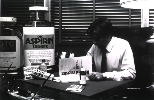 <p>An employee of the FDA sits at a desk and reads the Federal Register. On his desk are over-sized bottles of aspirin and other medications, toothpaste and Pepto-Bismol.</p>