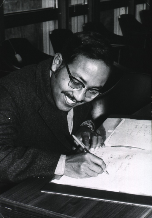 <p>Head and shoulders, right pose, seated at a desk, writing; wearing glasses.</p>