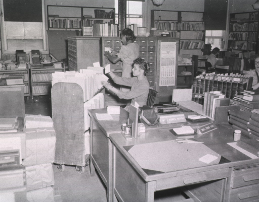 <p>Interior view: A bindery staffer is sitting in front of a book truck holding a catalog card while another is standing in front of the card catalog.  The desks of Mrs. Eddie Dent and Agnes Boush are in the foreground.  Bookshelves line the walls, wrapped bundles of library material are stacked on the floor.</p>