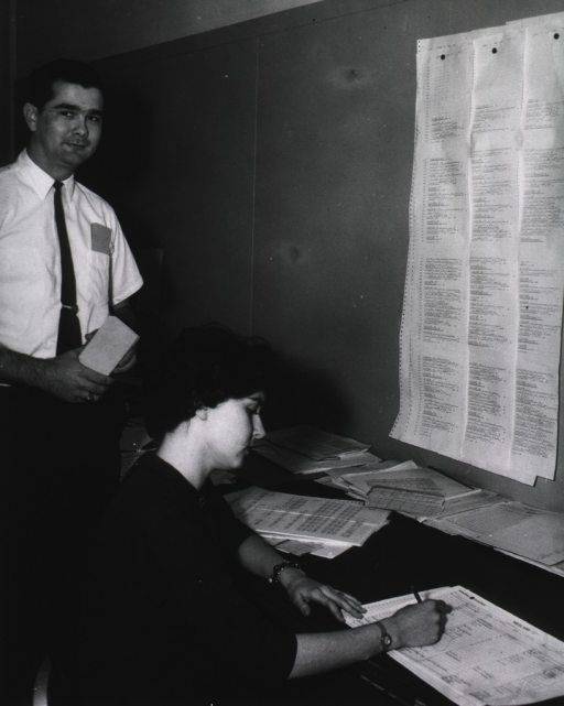 <p>Interior view: Robin Staley is writing on a data sheet.  Three rows of sheets are tacked onto the wall in front of her.  A man is standing next to her.  On the desk are punch cards and data sheets.</p>