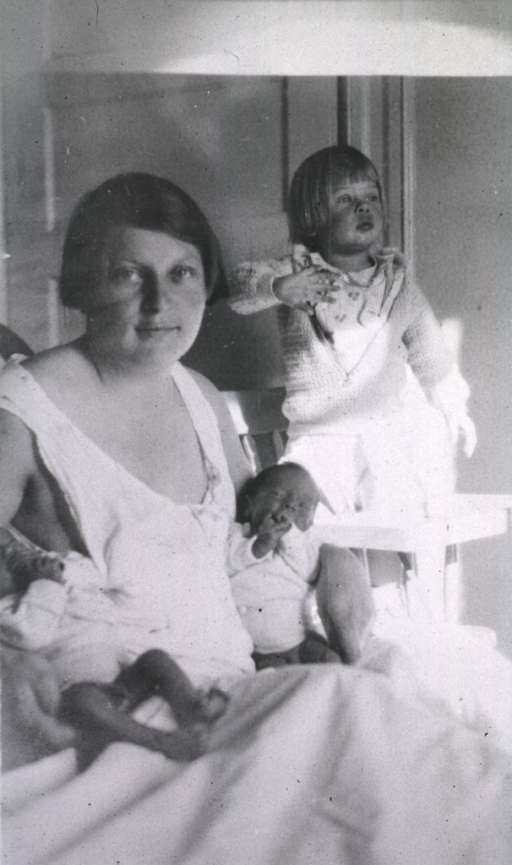 <p>A mother sits in bed holding her newborn twins while a daughter stands nearby.</p>