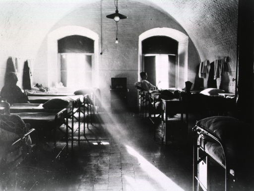 <p>A row of beds lines either wall of a sunlit room.  Several wounded servicemen are seen reclining in the beds (cf. photograph no. 1 in this box).</p>
