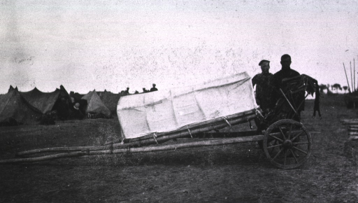<p>A view of a covered wheeled travois used in the transportation of sick and wounded, two soldiers(?) stand nearby.</p>