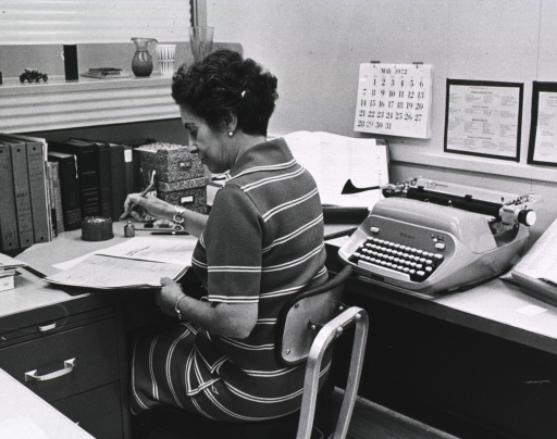 <p>Interior view: Dora Rivera is sitting at her desk.  On the desk are reference books shelved upside down, two boxes of file cards, a book holder, and a manual typewriter.  On the wall is a calendar for May 1972.</p>