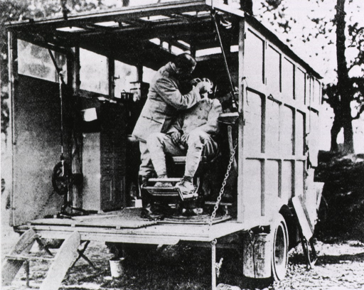<p>An army dentist treats his patient on the back of an army truck.</p>