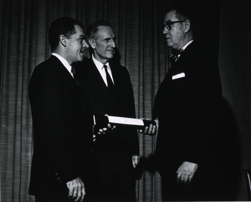 <p>Dr. Robert F. Goheen is shown presenting a Rockefeller Public Service Award for 1964 to Dr. James A. Shannon.  Also present is John D. Rockefeller 3rd.</p>