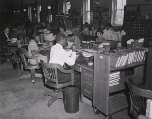 <p>Interior view: Staff review material that has been returned from the bindery.  Bookshelves line the wall, a card catalog is in front of the shelves, and material is on book trucks.</p>