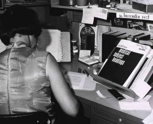<p>Interior view: Literature analyst at desk.  On the desk are language dictionaries, a tab binder, a copy of the January 1974 Index Medicus Medical Subject Headings.</p>