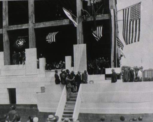 <p>Cornerstone is being lowered into position; a group of dignitaries stand on a low grandstand; American Flags hang from the building; many people are gathered to witness the event.</p>