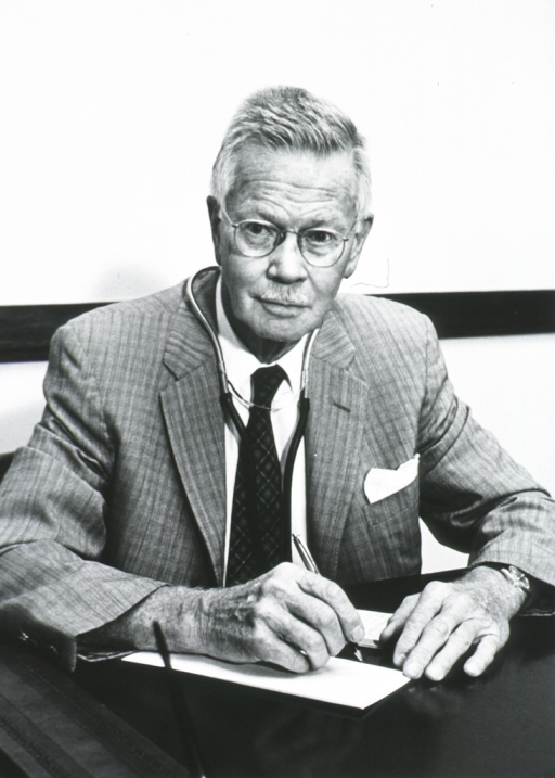 <p>Half length, full face, seated at a desk writing, wearing suit, stethoscope around his neck.</p>