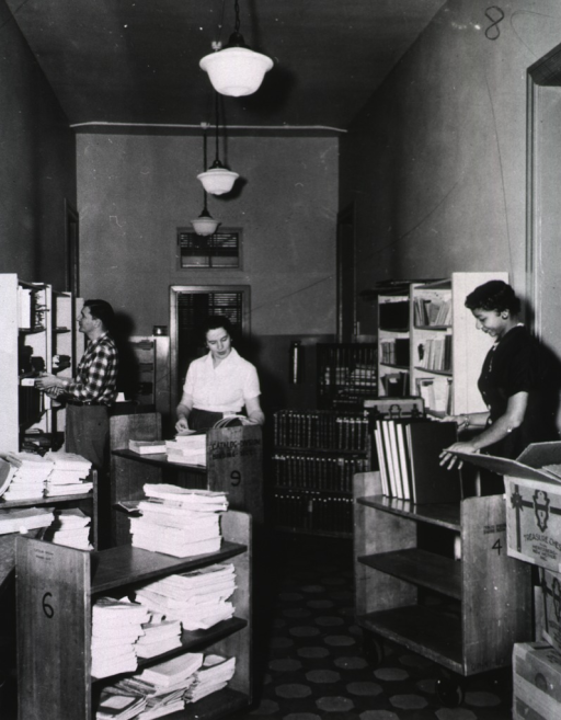 <p>Interior view: Catalog Division, Binding Section.  Staff at book trucks and shelf.</p>