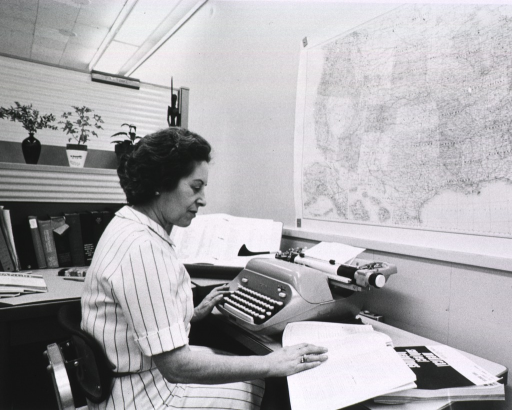 <p>Interior view: Mrs. Timbe is sitting in front of a manual typewriter.  Some reference works on her desk are shelved upside down.  A map of the U.S. is in front of her.  Beneath the material she is looking at is a copy of medical subject headings.</p>
