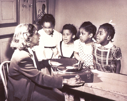 <p>Four African American girls sing along with the nursery school worker and a vinyl record on the record player.</p>